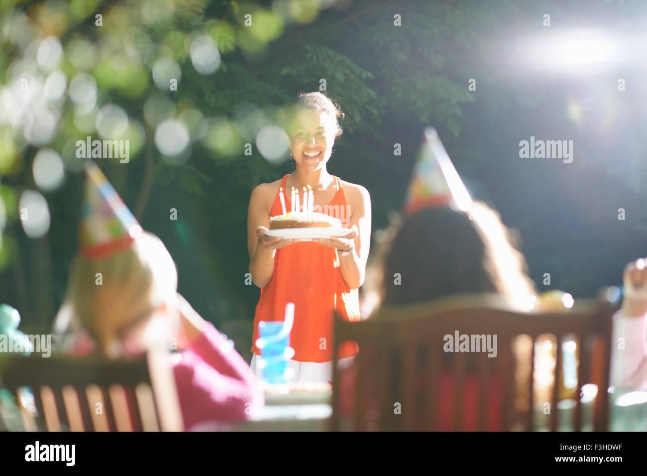 Madre con pastel de cumpleaños a la mesa en el jardín fiesta de cumpleaños Imagen De Stock