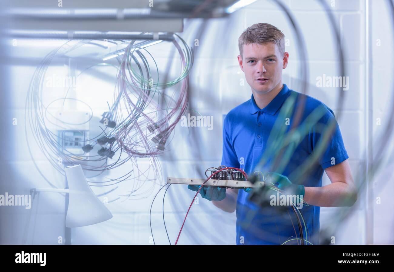Retrato de aprendiz trabajador electrónica en electrónica fábrica, Imagen De Stock