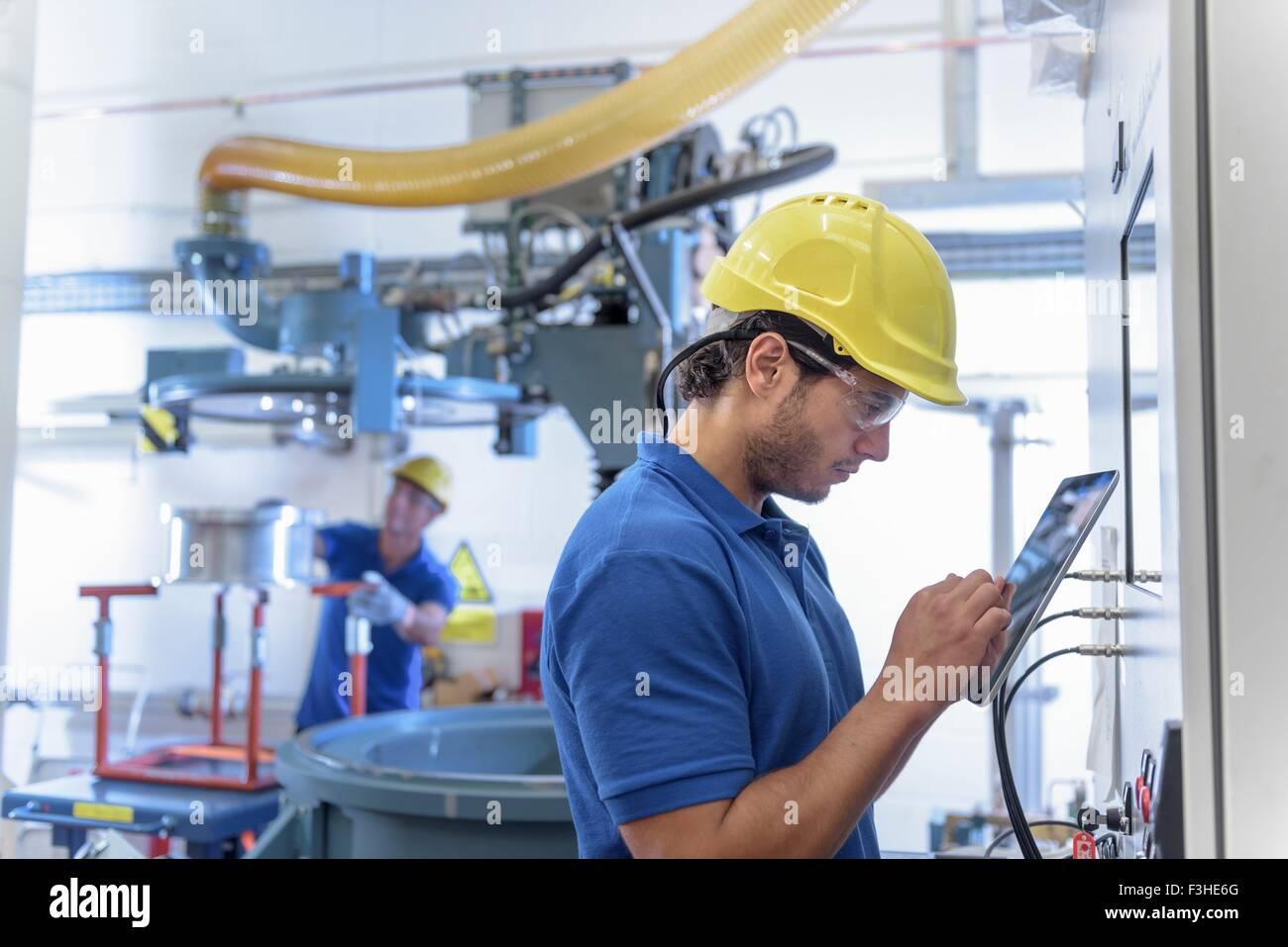 Los trabajadores que operan con equipos de pruebas ambientales en tableta digital electrónica fábrica Imagen De Stock