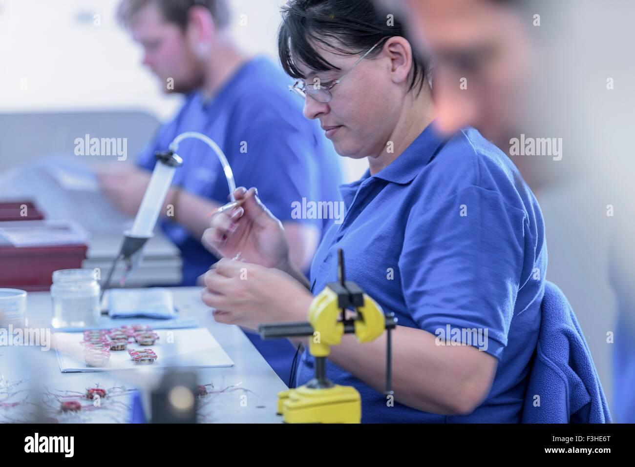Trabajadora montaje de electroimanes en la línea de producción en la fábrica de electrónica Imagen De Stock