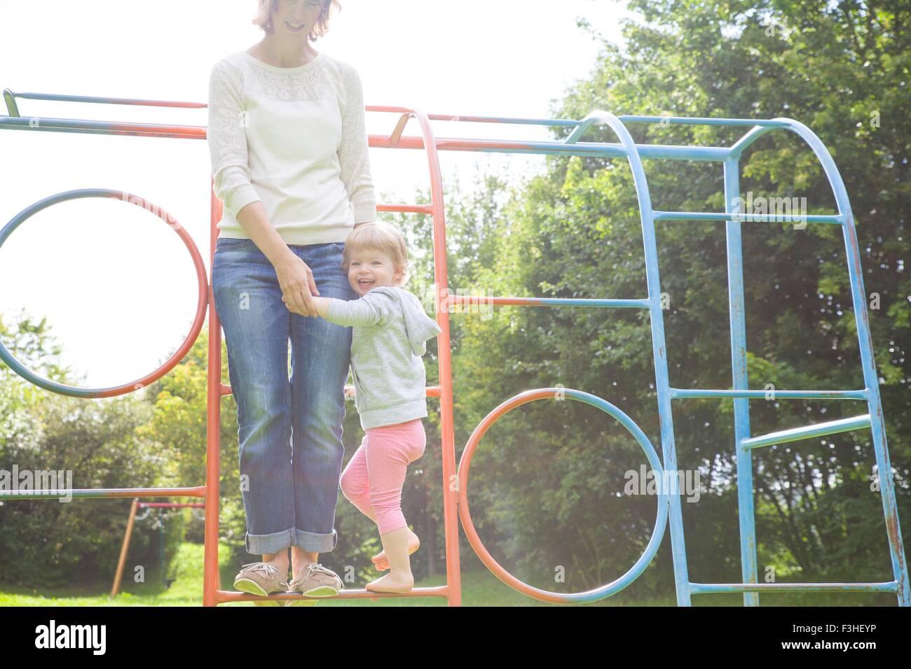 Madre y mujer niño jugando en columpios Foto de stock