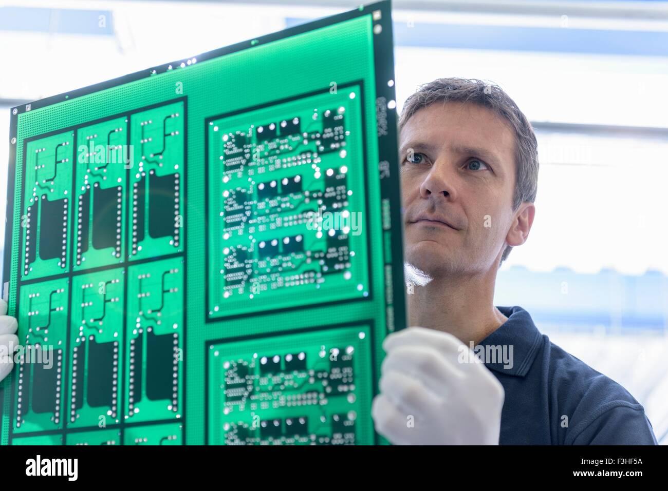 Placa de circuito de inspección del trabajador durante el proceso de fabricación en fábrica de placa Imagen De Stock