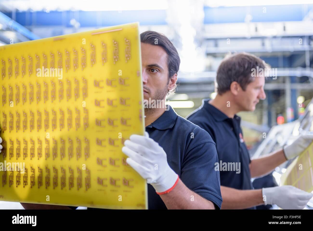Los trabajadores la inspección durante la fabricación de placa de circuito en el circuito impreso factory Imagen De Stock