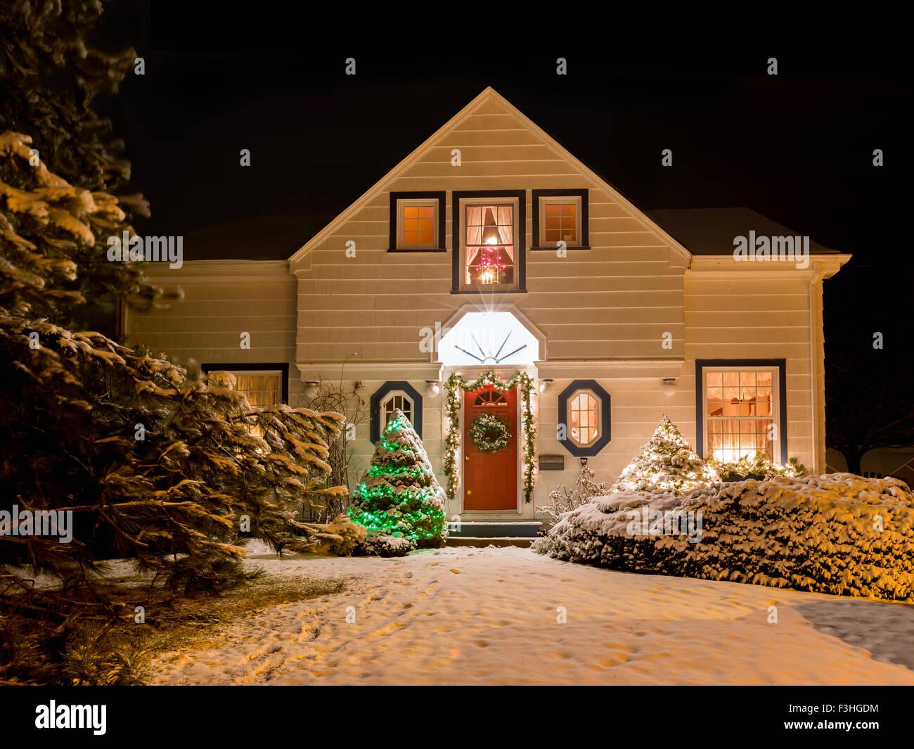 Una casa decorada con una corona, garland y luces de Navidad en una clara noche de invierno. Imagen De Stock