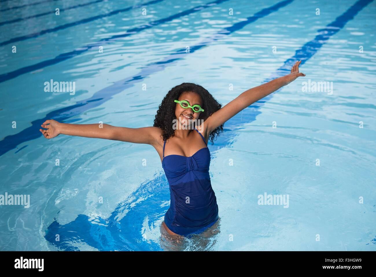 Retrato de niña de pie en la piscina llevar gafas de natación, con los brazos en alto, mirando a la cámara Imagen De Stock