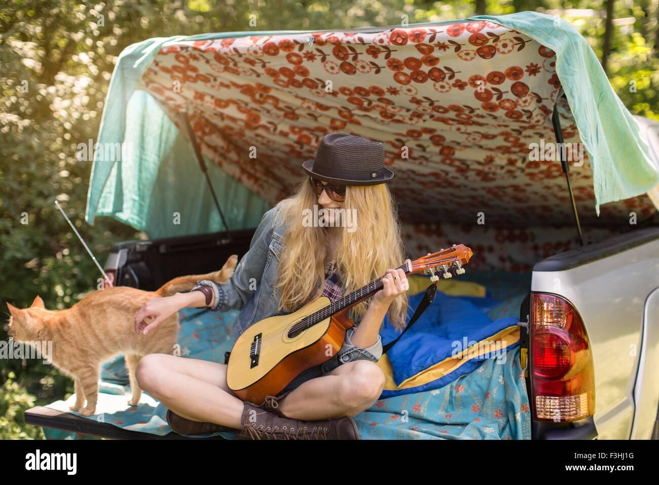 Mujer joven acariciándole cat y tocando ukulele mientras camping en pick up boot Imagen De Stock