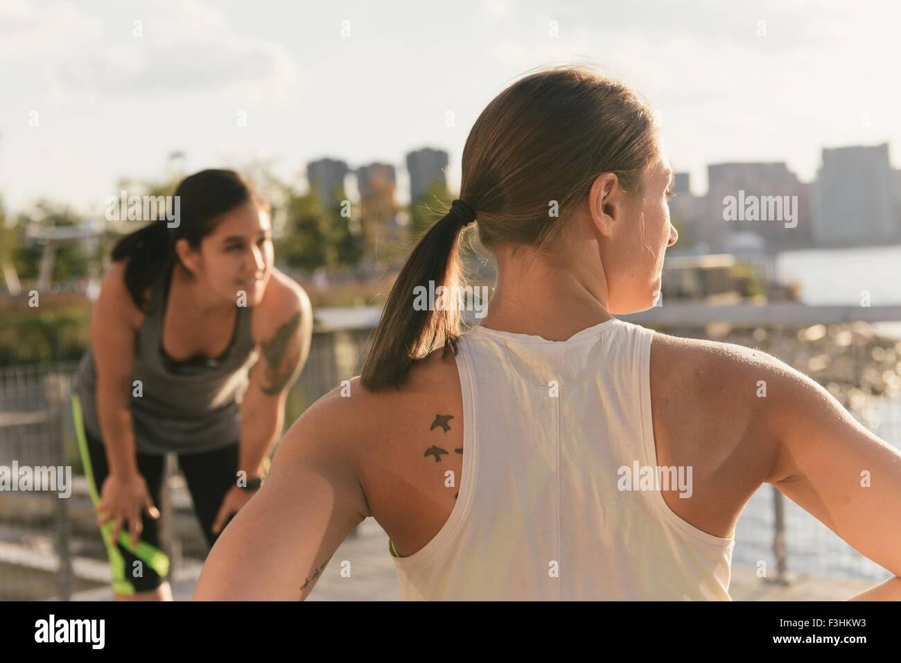 Dos amigos hablando después de ejercitarse juntos en la ejecución de ropa junto al río Imagen De Stock