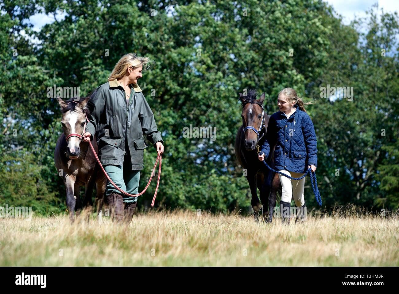 Madre e hija caminando los caballos en el campo Foto de stock