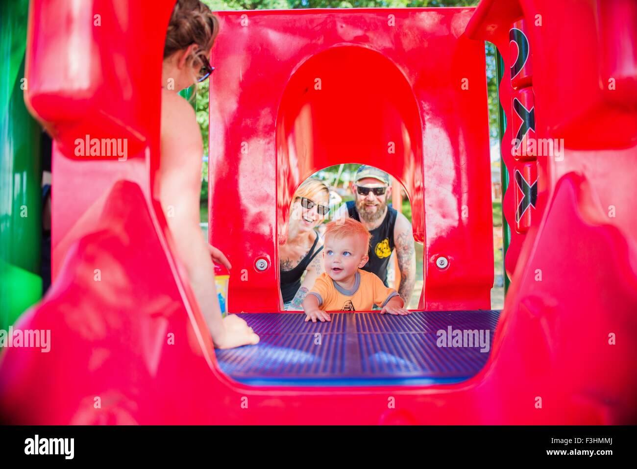 Vista a través de equipos de juego de la madre y el padre alentador baby boy Foto de stock