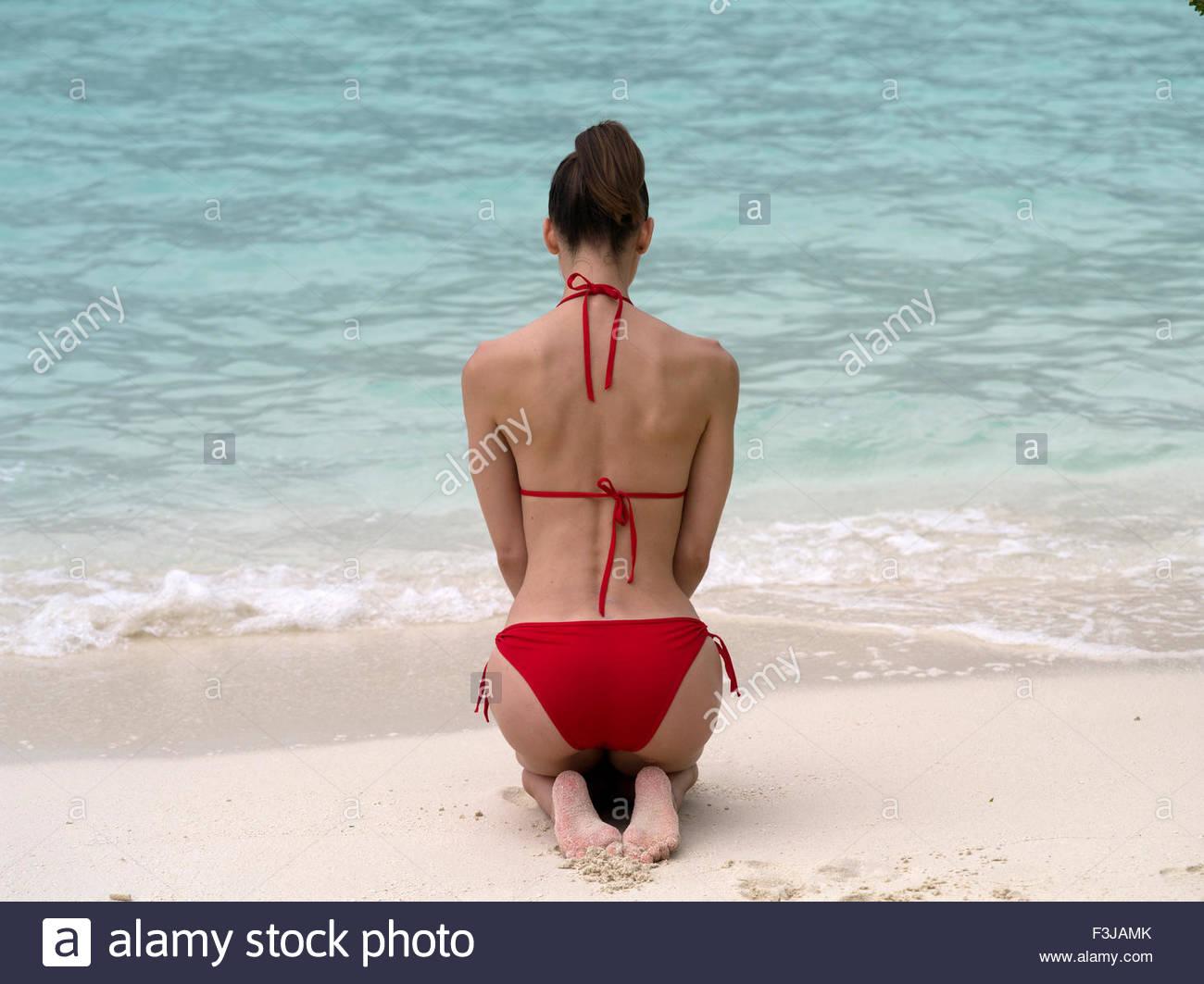 410521165645 Vista trasera de una mujer arrodillada con espalda desnuda vistiendo ...