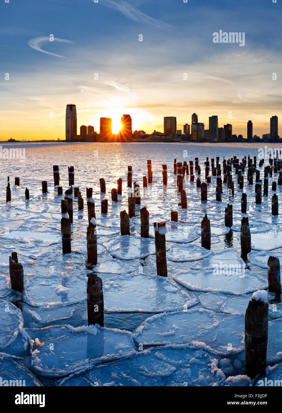 Pilotes de madera desde Nueva York viejo muelle que sobresalen a través del hielo sobre el Río Hudson Imagen De Stock