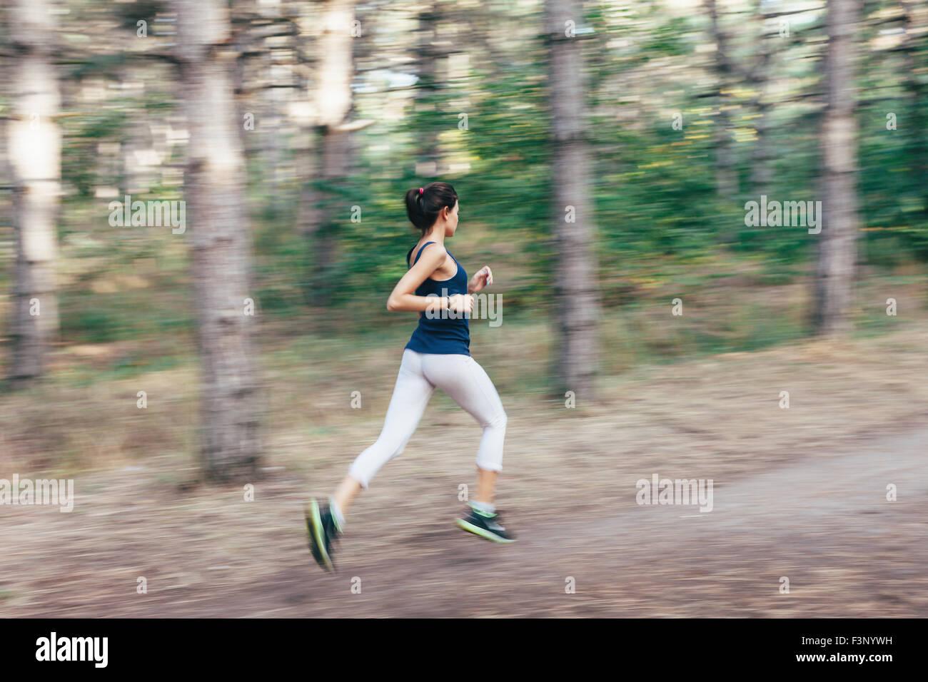 Mujer joven corriendo en un camino rural al atardecer en otoño del bosque. Antecedentes deportivos en el estilo Imagen De Stock