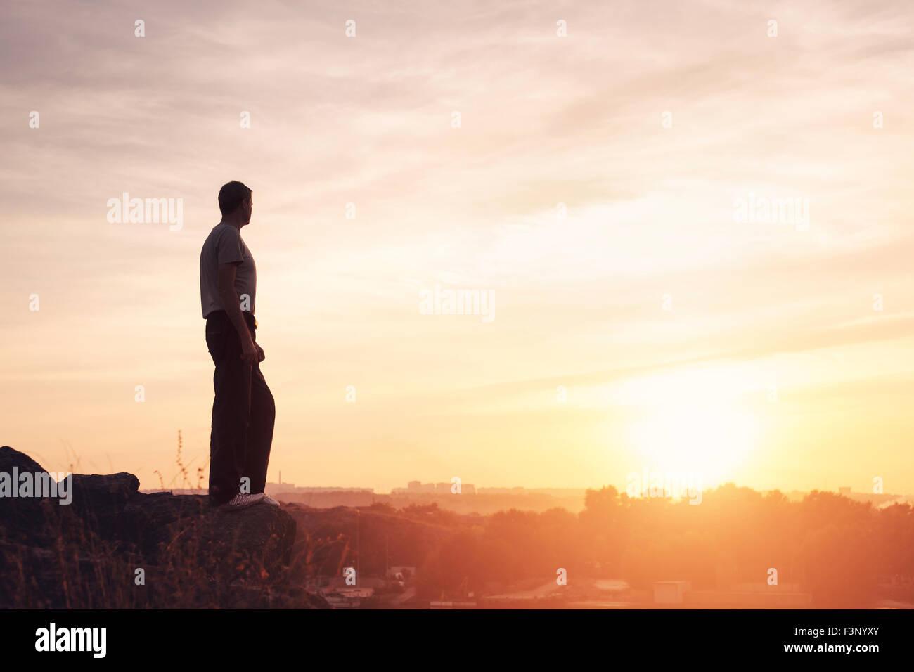 Silueta de un hombre con los brazos arriba planteadas en el hermoso atardecer en la montaña. Antecedentes Imagen De Stock
