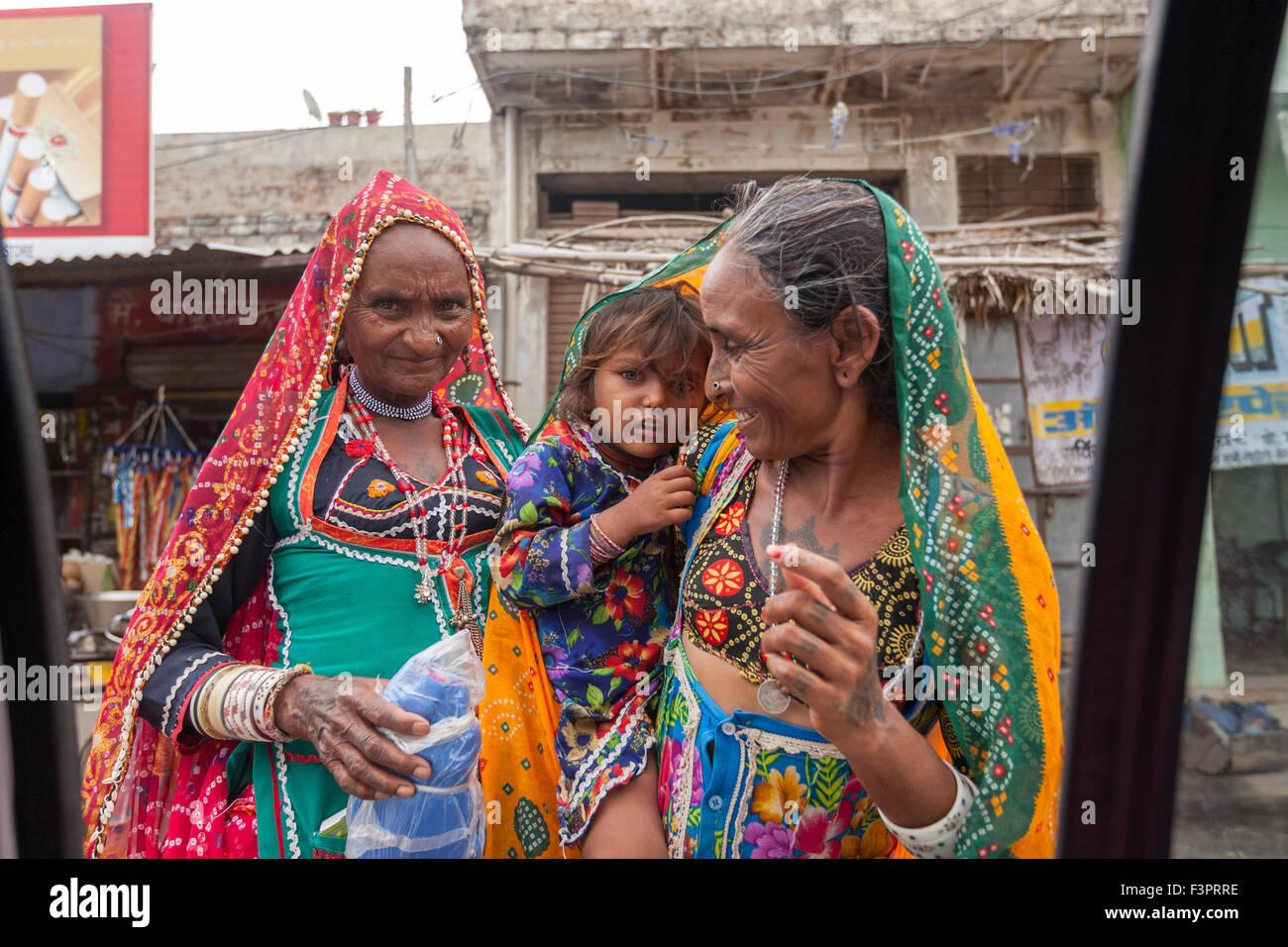 Rajasthani mujeres vestidas con trajes típicos que muestra a un niño a un turista en un taxi. Foto de stock