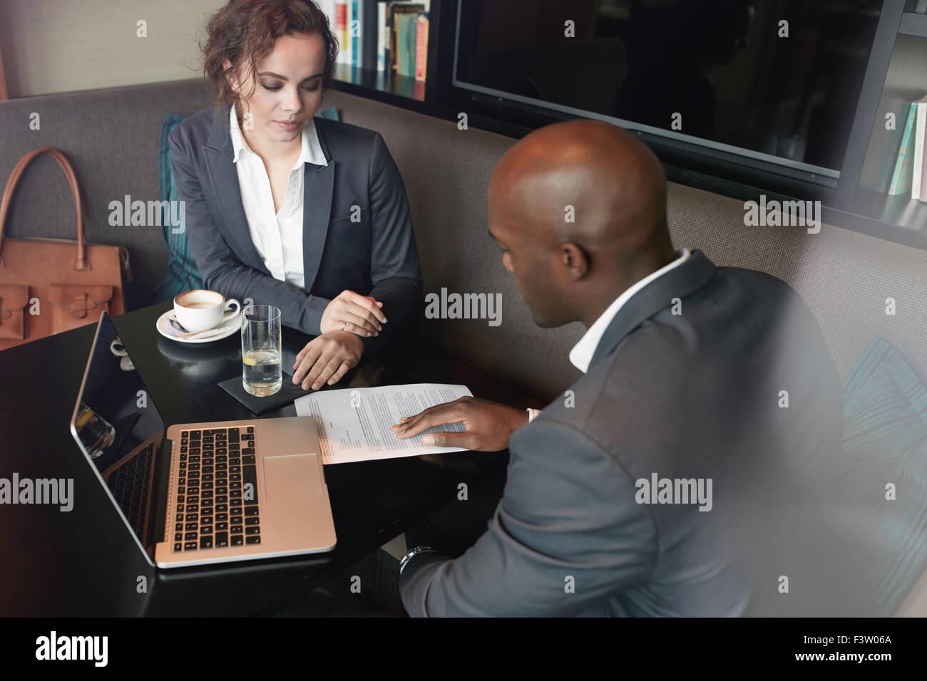 Los jóvenes discutir la estrategia comercial de café. Reunión de socios de negocios a lo largo de Imagen De Stock