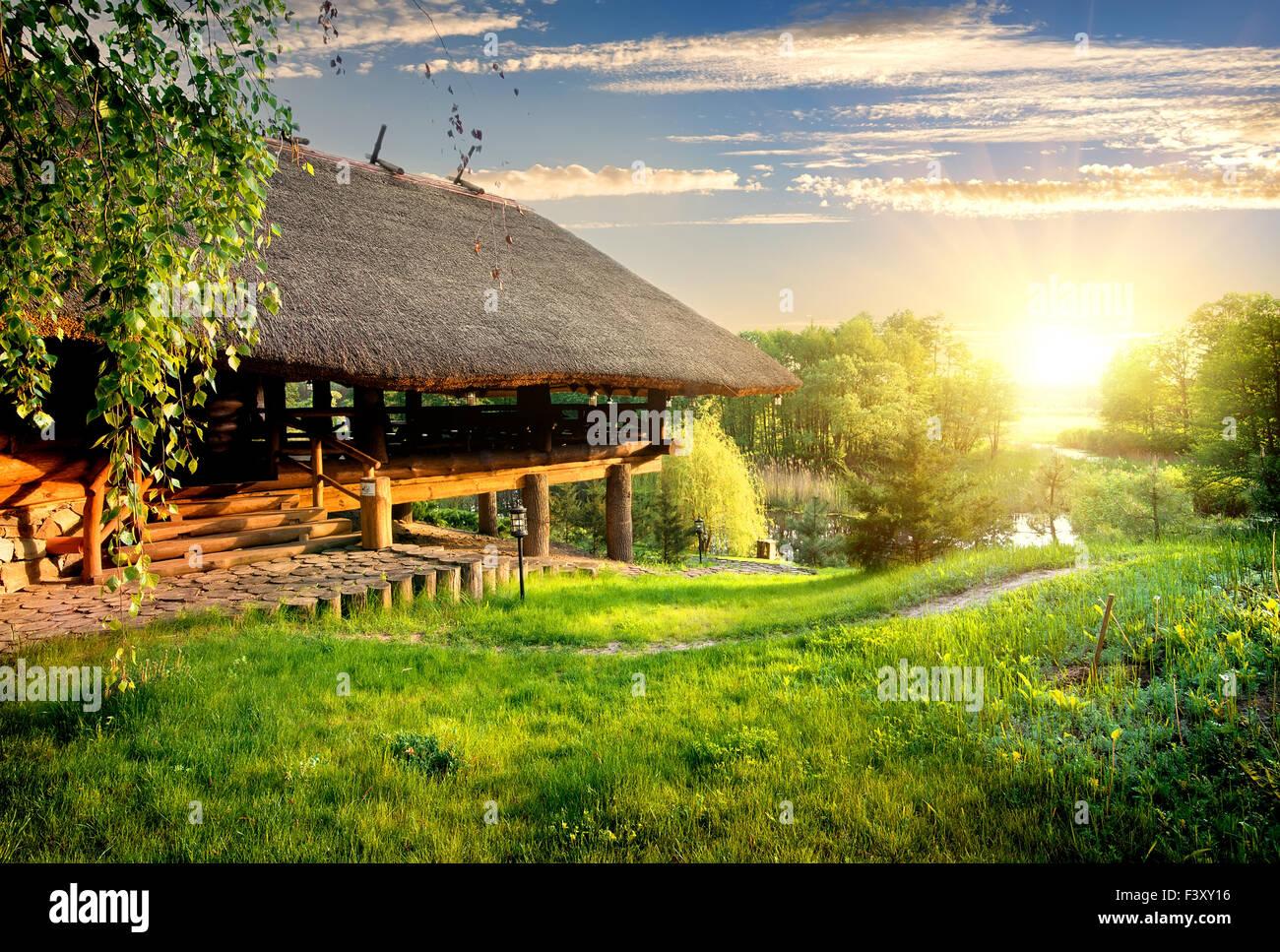 Casa de log, cerca del lago al atardecer Imagen De Stock