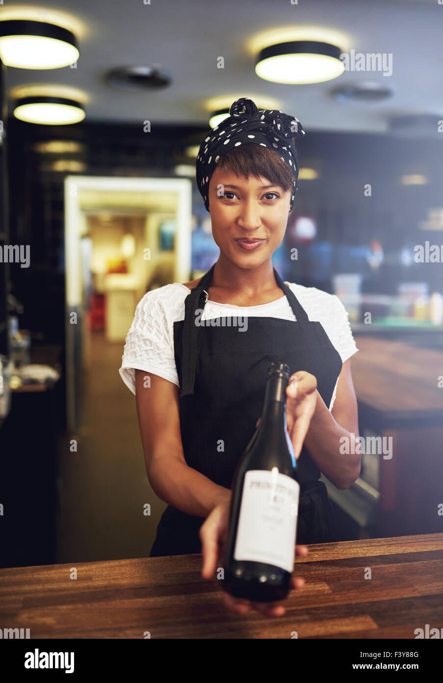 Sonriente joven camarera presentando una botella de vino tinto a un cliente para su aprobación antes de abrirlo, Imagen De Stock