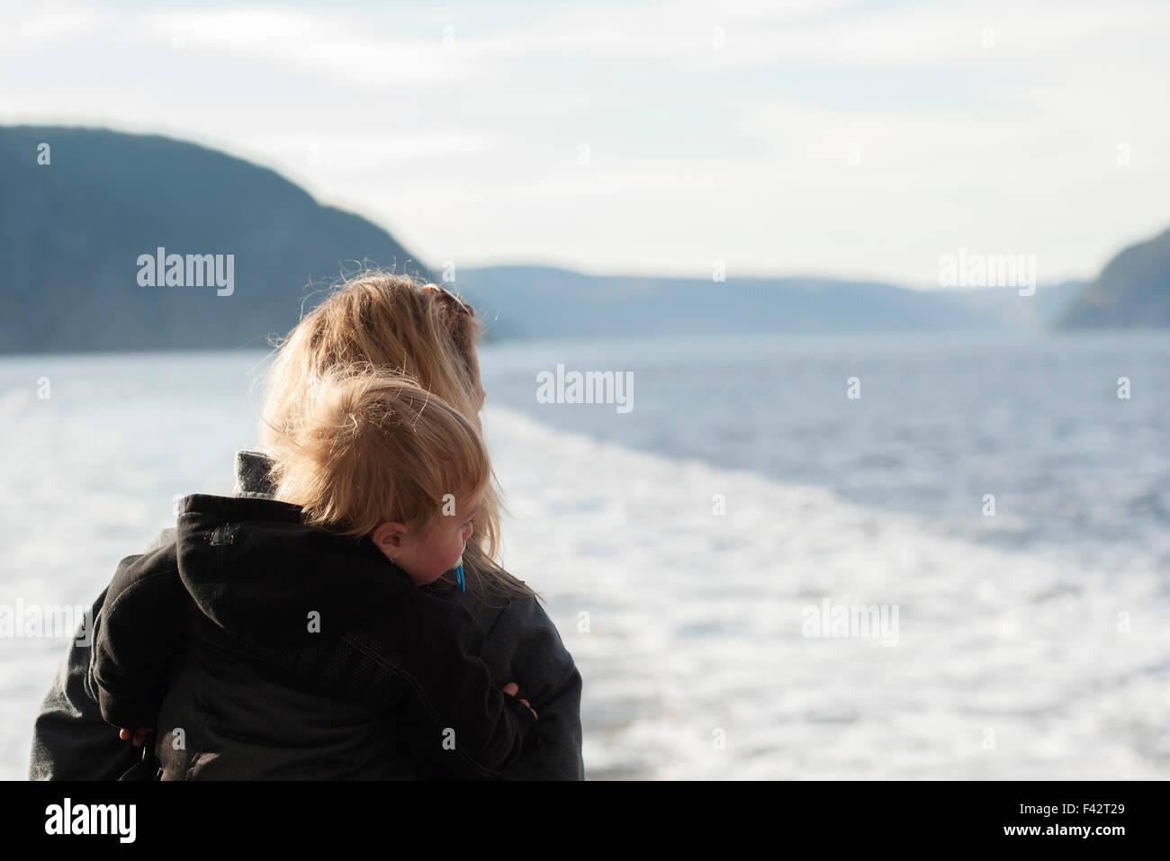 Madre e hijo mirando al tranquilo lago ver Imagen De Stock