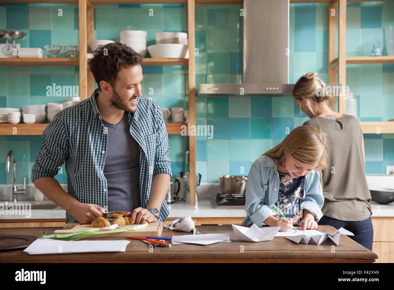 Dibujo joven hija ar cocina mientras los padres se preparan comida Imagen De Stock