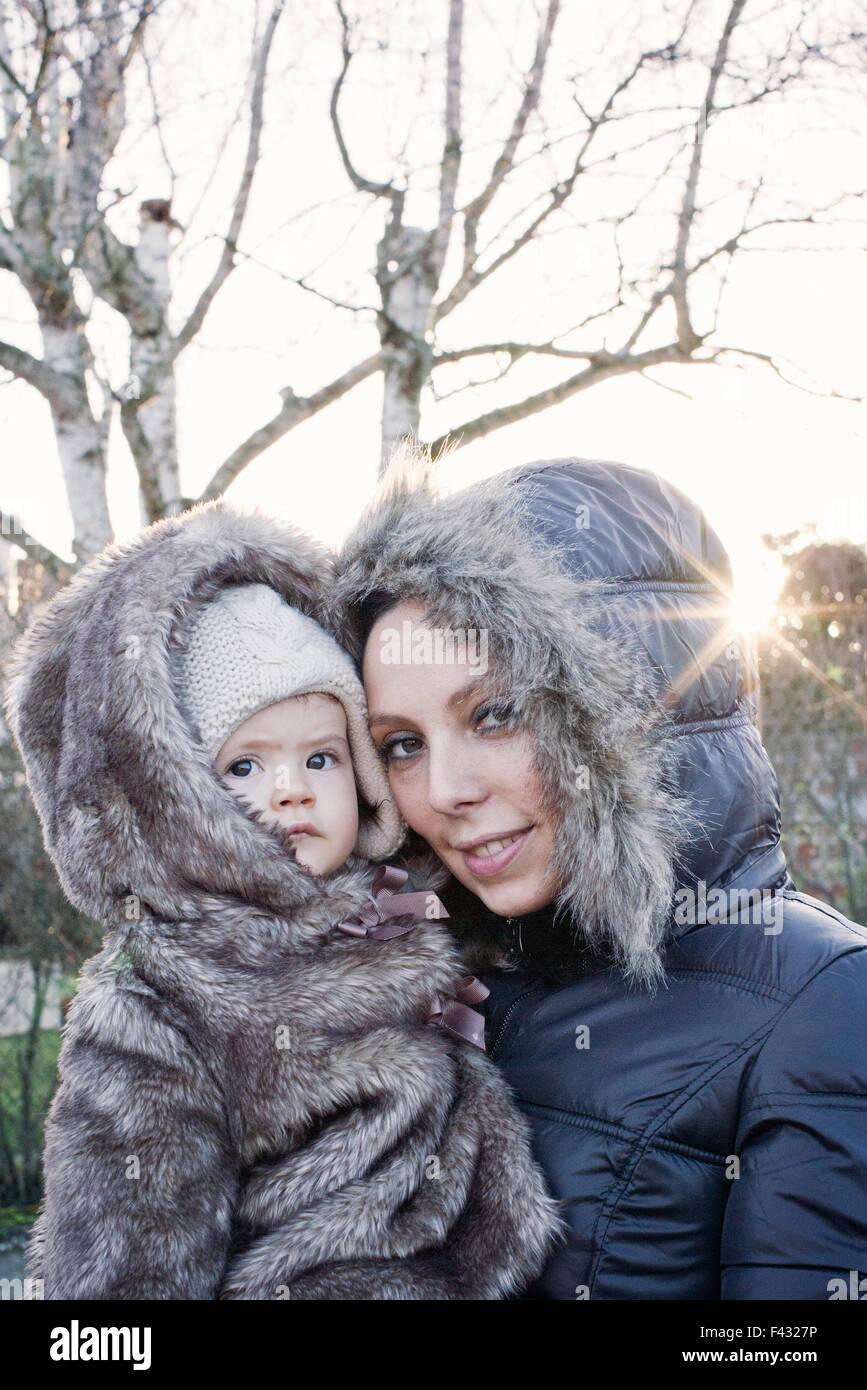 Niña Madre sosteniendo al aire libre, ambos vistiendo abrigos de invierno, Retrato Imagen De Stock