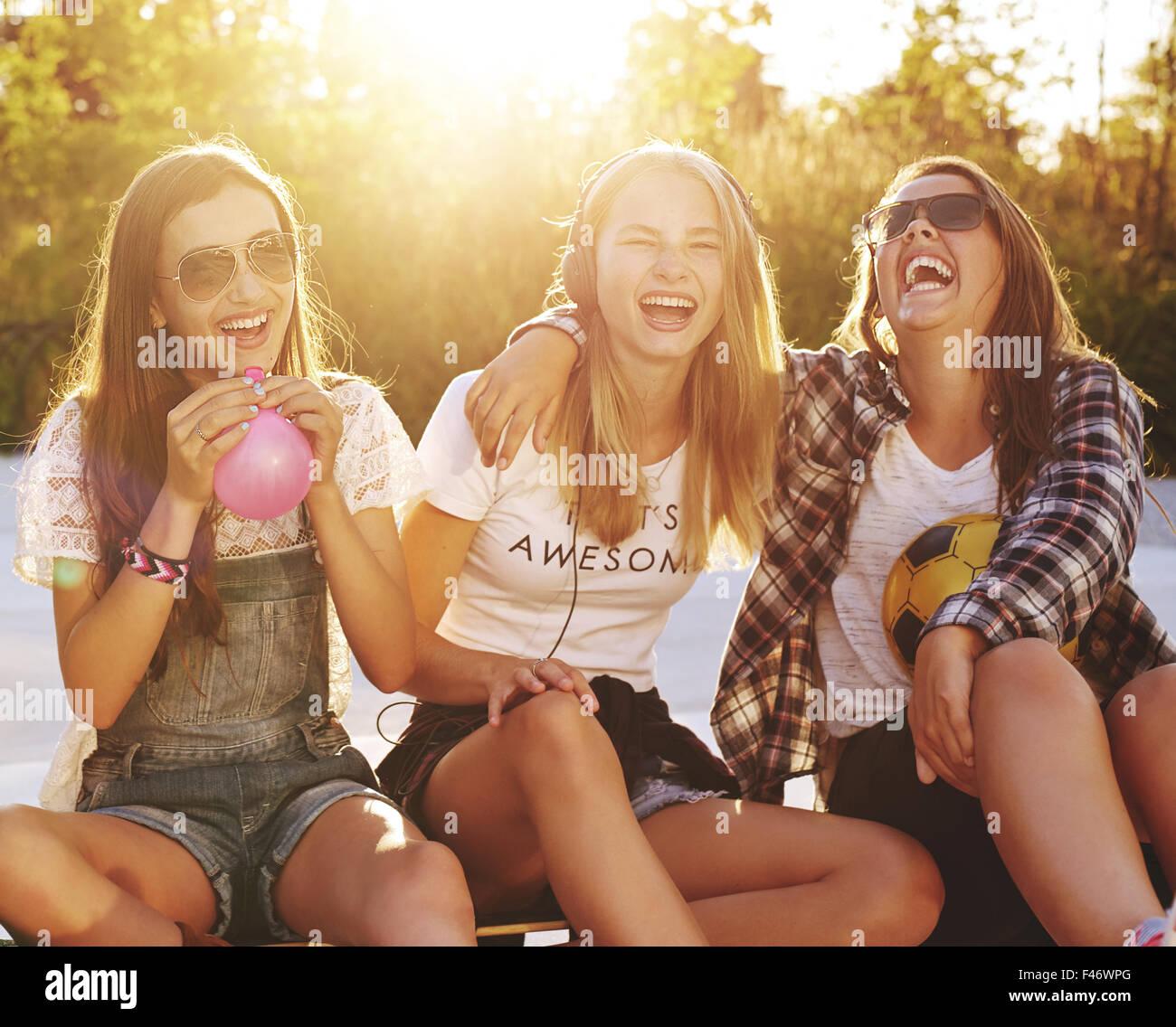 El grupo de niñas riendo mientras está sentado afuera disfrutando del verano Imagen De Stock