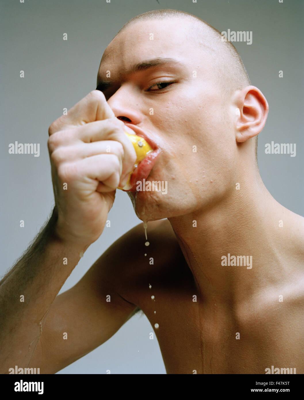 Hombre se desnudó hasta la cintura comiendo un limón. Imagen De Stock