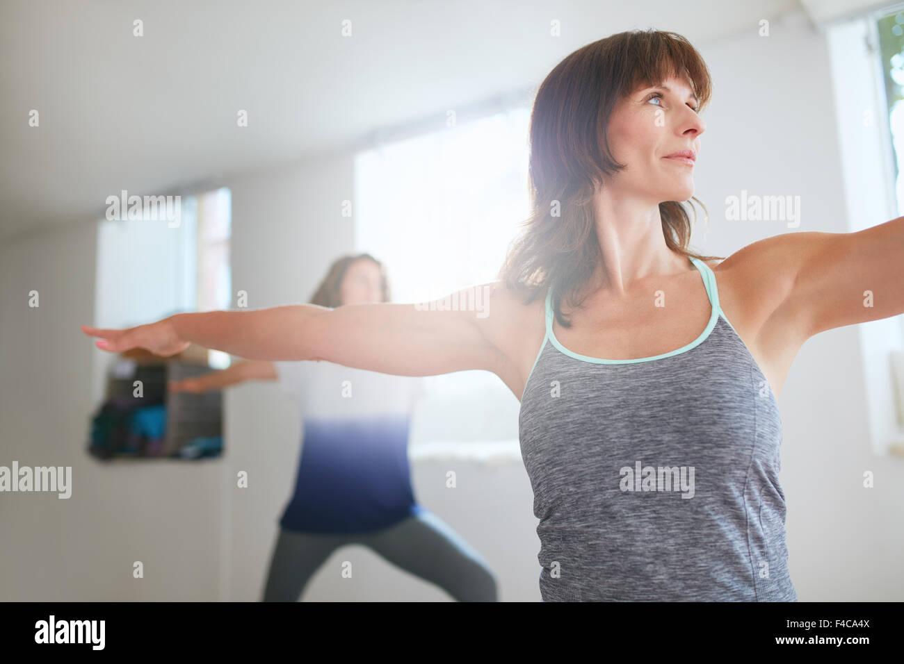 Foto de mujer fitness hacer yoga. Las mujeres ejerzan en clase de yoga. Virabhadrasana pose. Imagen De Stock
