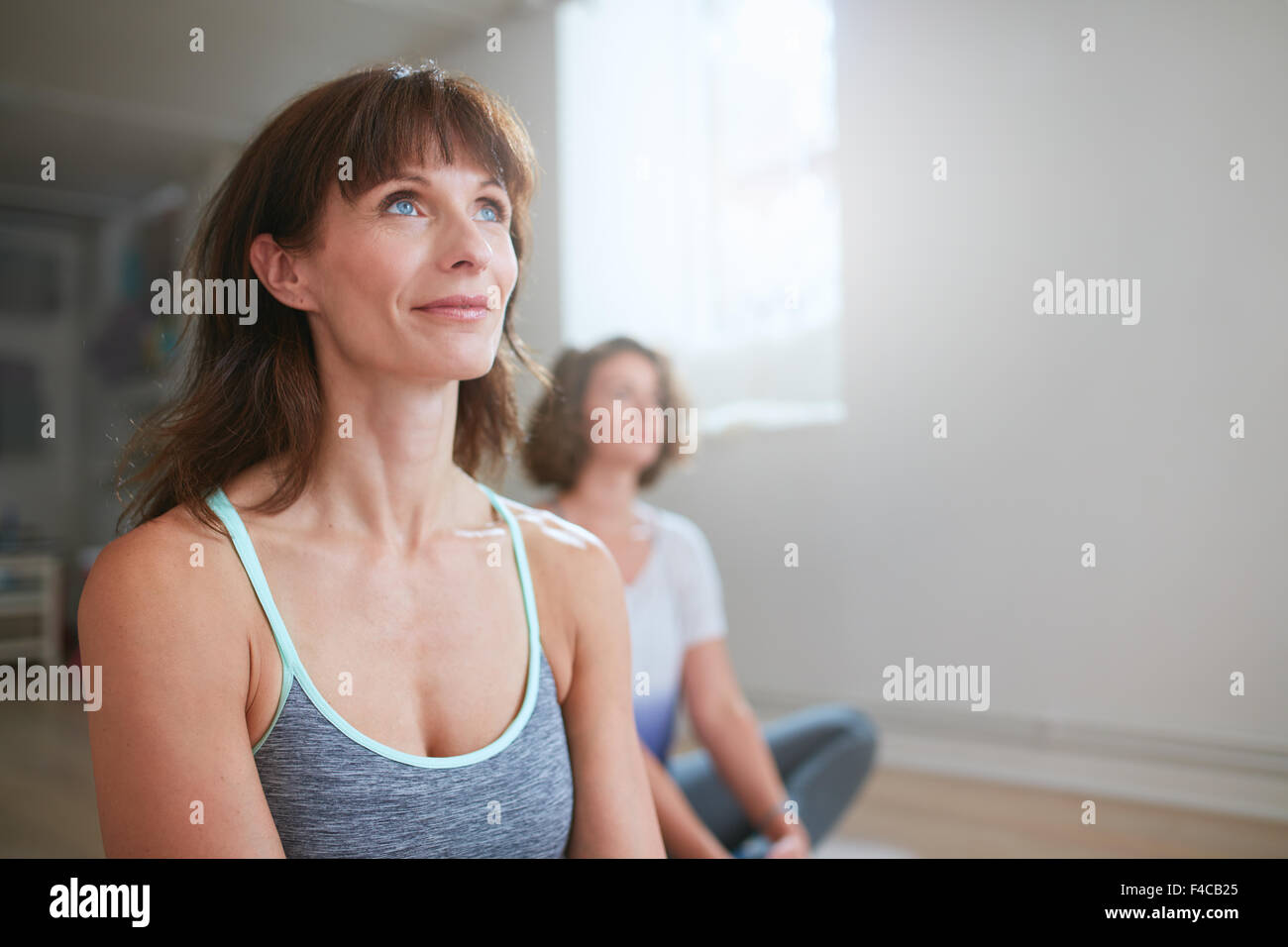 Retrato de mujer sentada en el piso de fitness en clase de yoga mirando a otro lado. Instructor de yoga durante Imagen De Stock