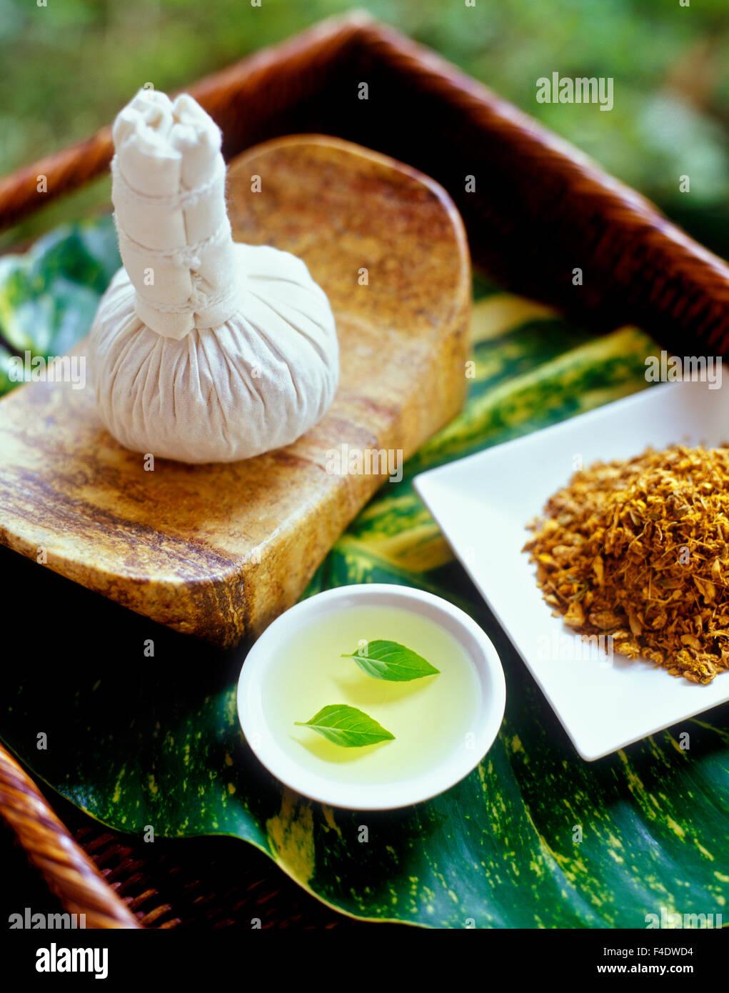 Ingredientes para una cataplasma caliente masaje. Las hojas de albahaca en aceite de semilla de uva, y cataplasma.Riviera Foto de stock