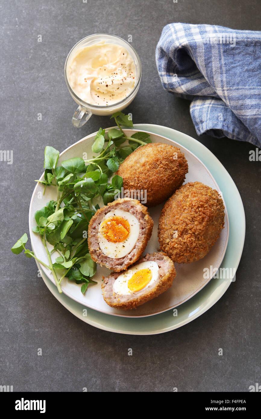 Scotch huevos en un plato con berros ensalada y mayonesa dip Foto de stock