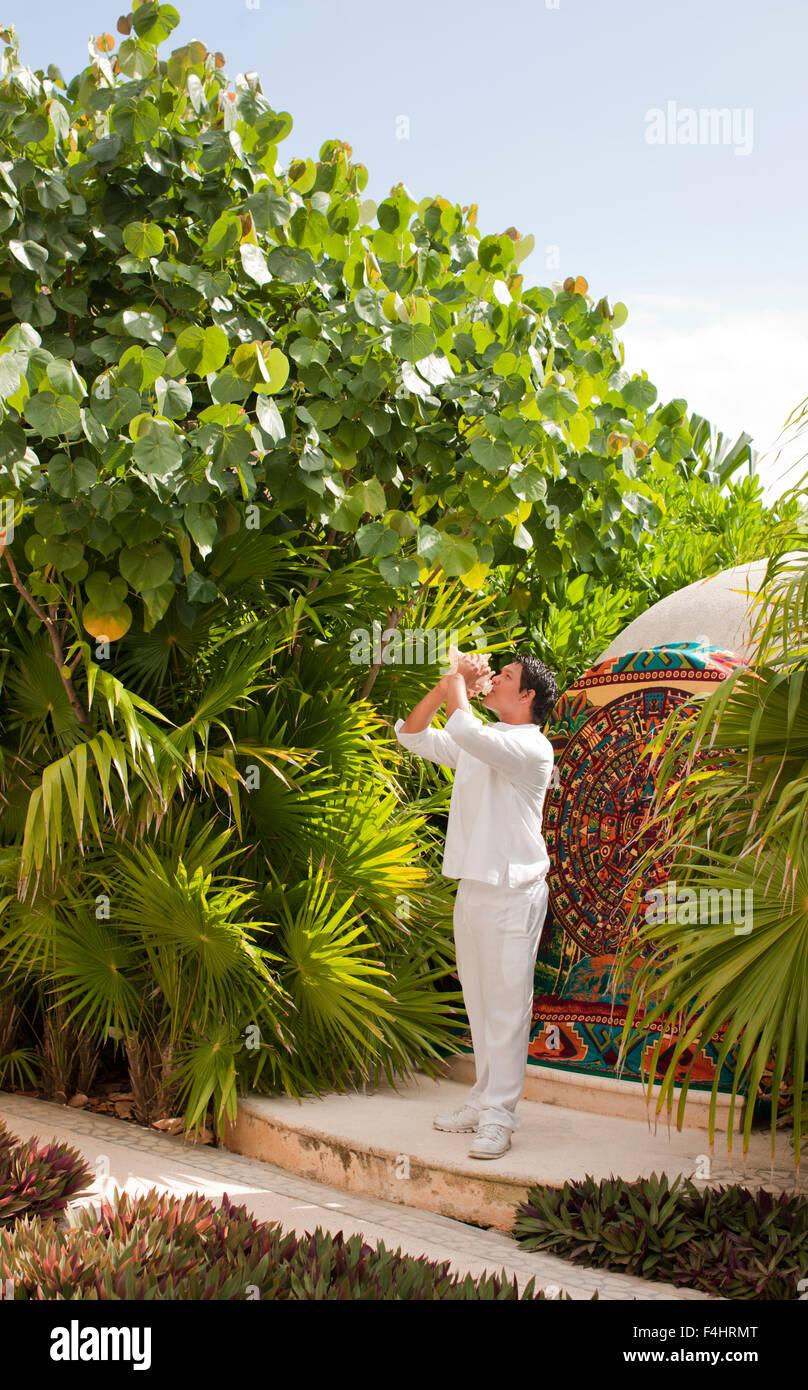 Un joven mexicano hombre sopla una caracola para indicar el inicio del Temazcal tratamiento en spa Aqua en Live Imagen De Stock