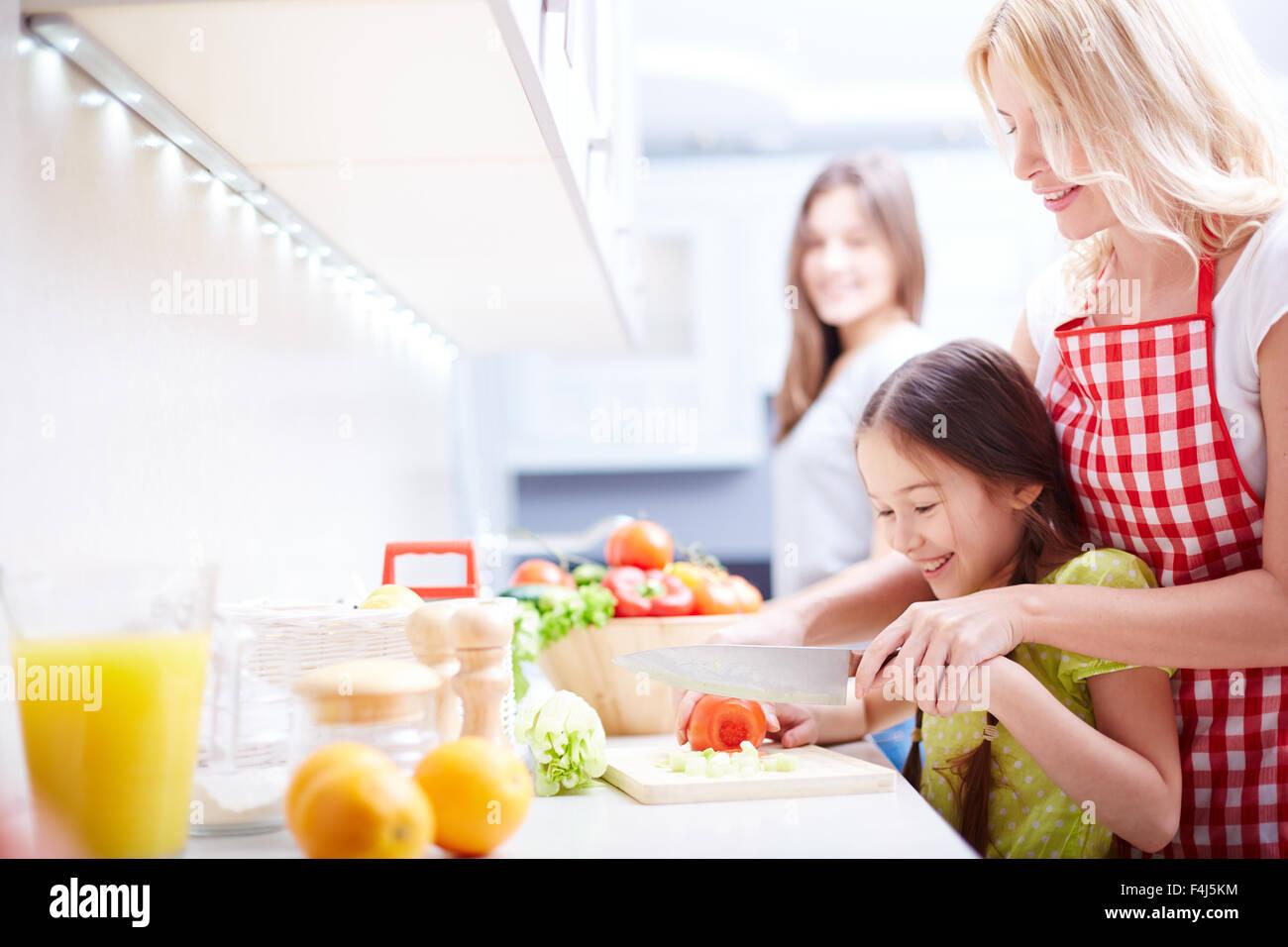 Mujer joven que ayudaba a su hija tomate picado en la cocina Foto de stock