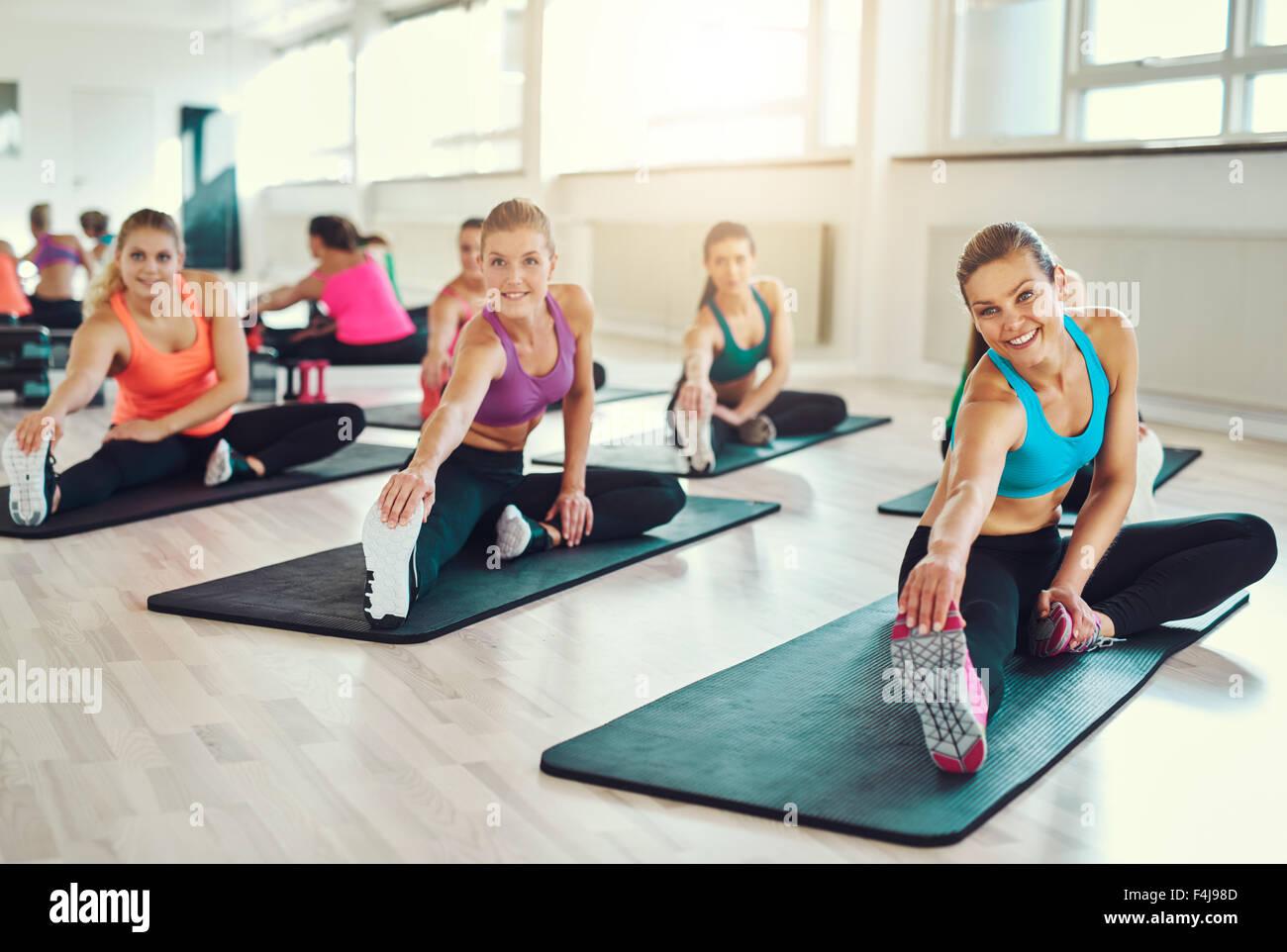 Grupo de mujeres jóvenes en la clase de aeróbicos en el gimnasio haciendo ejercicios de estiramiento para Imagen De Stock