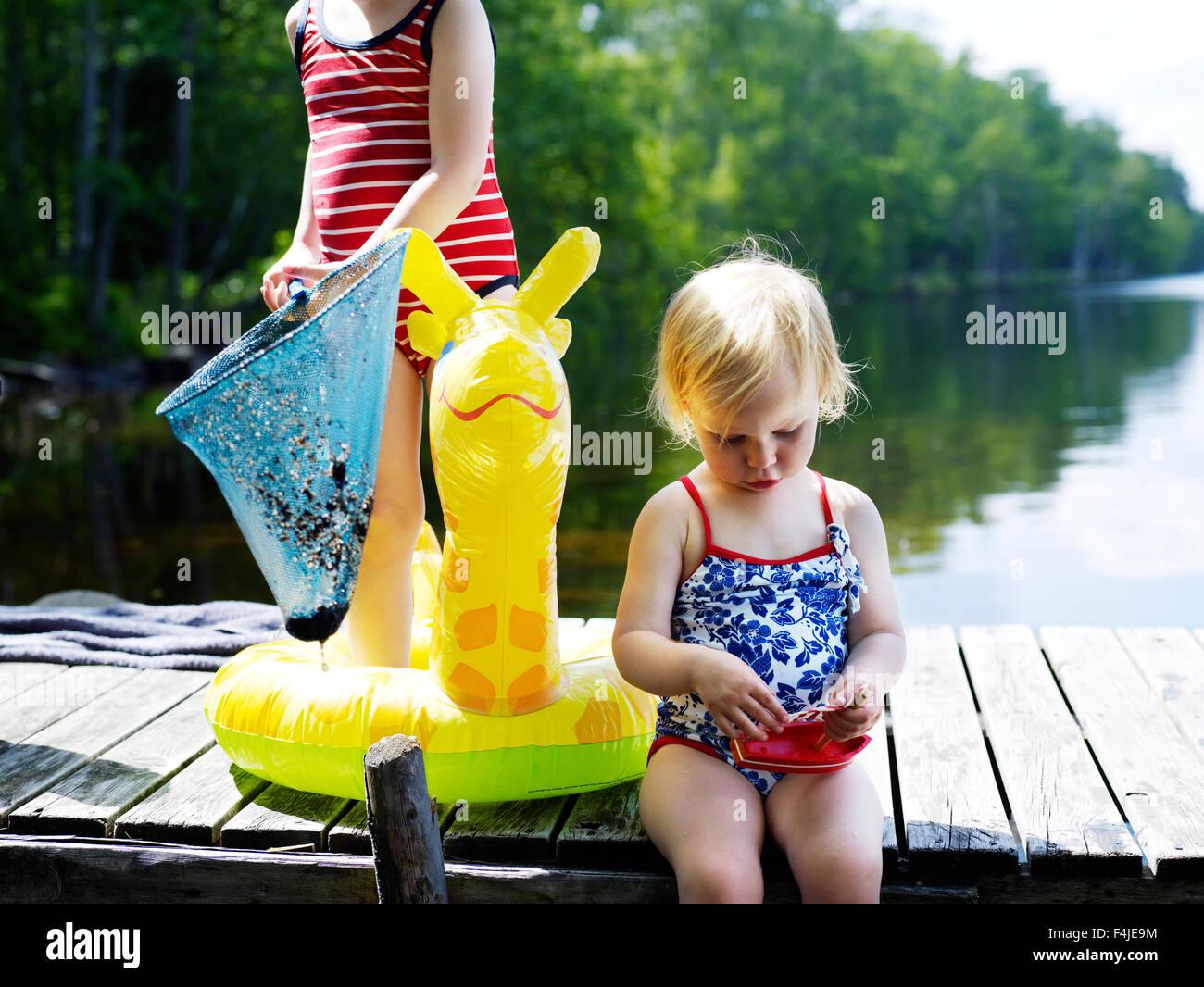 Escandinavia, Suecia, dos niñas (2-5) en el muelle la celebración de juguete y red de pesca Foto de stock
