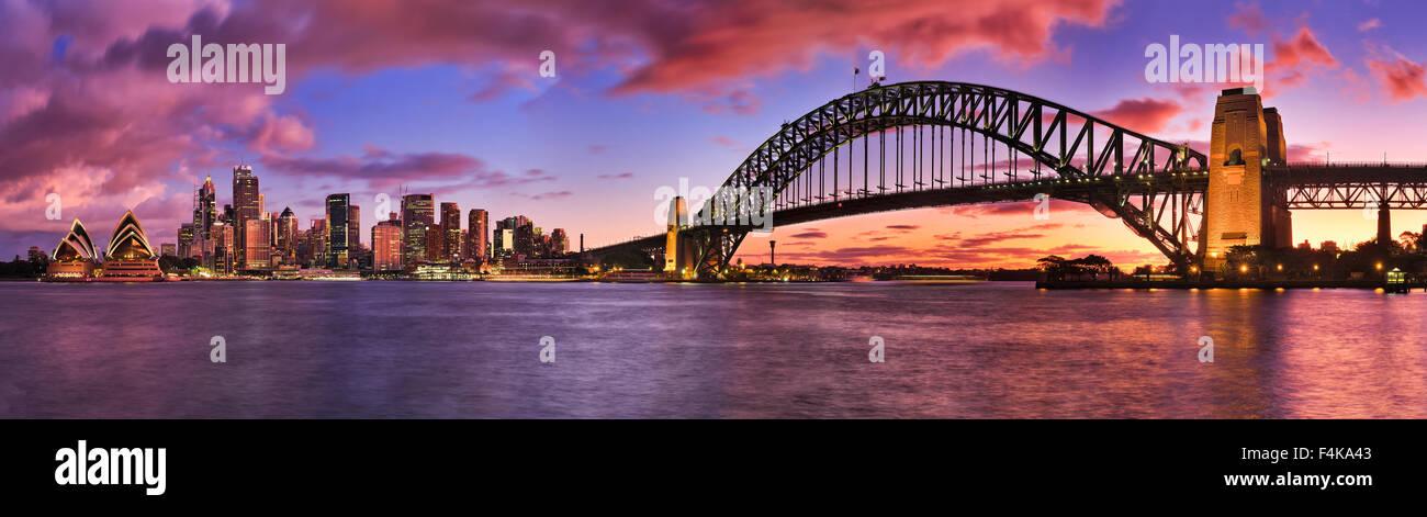 Quema luminoso atardecer en Sydney CBD cityline panorámicamente representada a través de puerto incluyendo rascacielos y Harbour Bridge Foto de stock