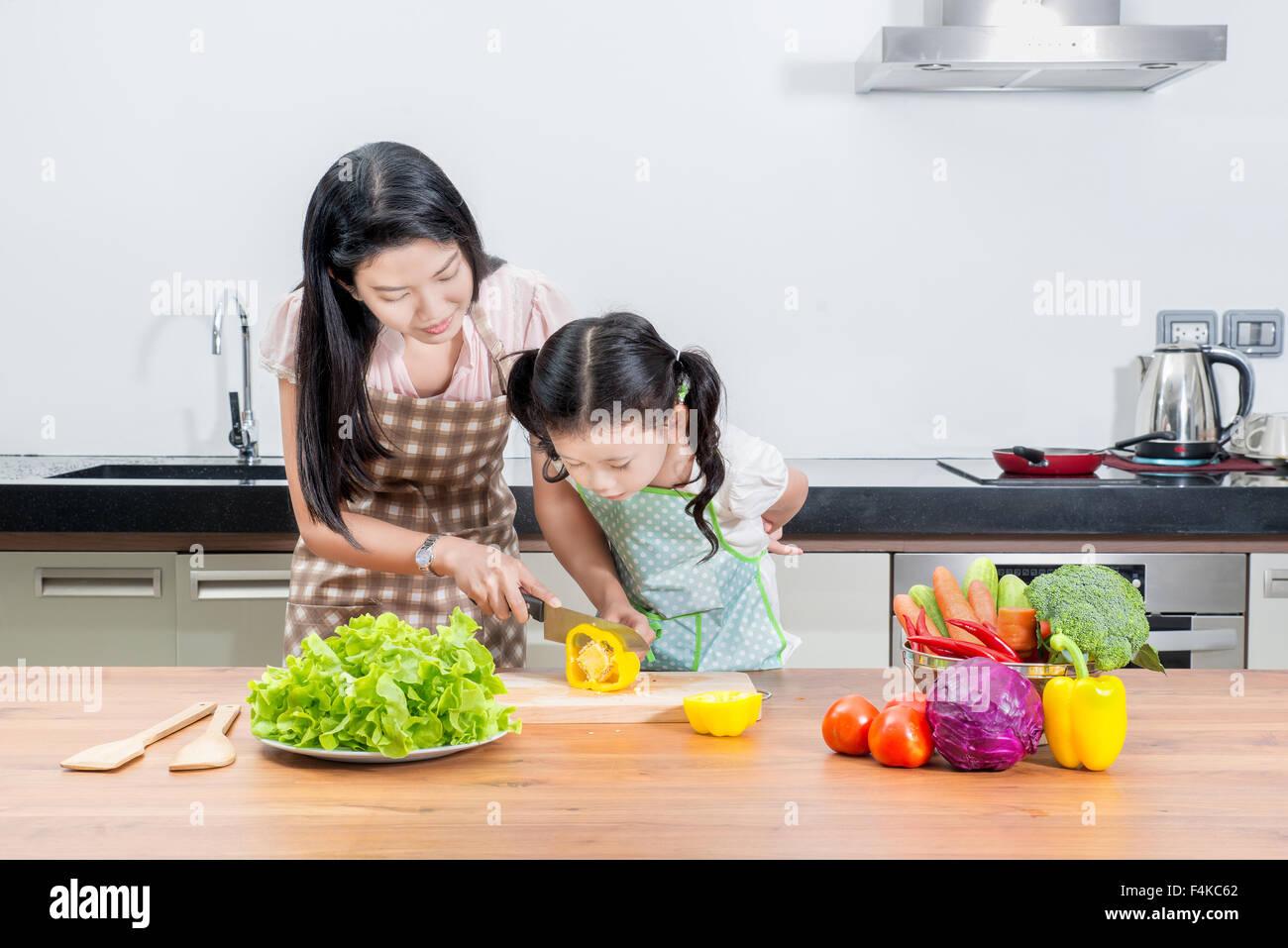 La familia, la infancia y la gente feliz concepto asiático - Madre e hija kid cocinar en la cocina de casa Foto de stock