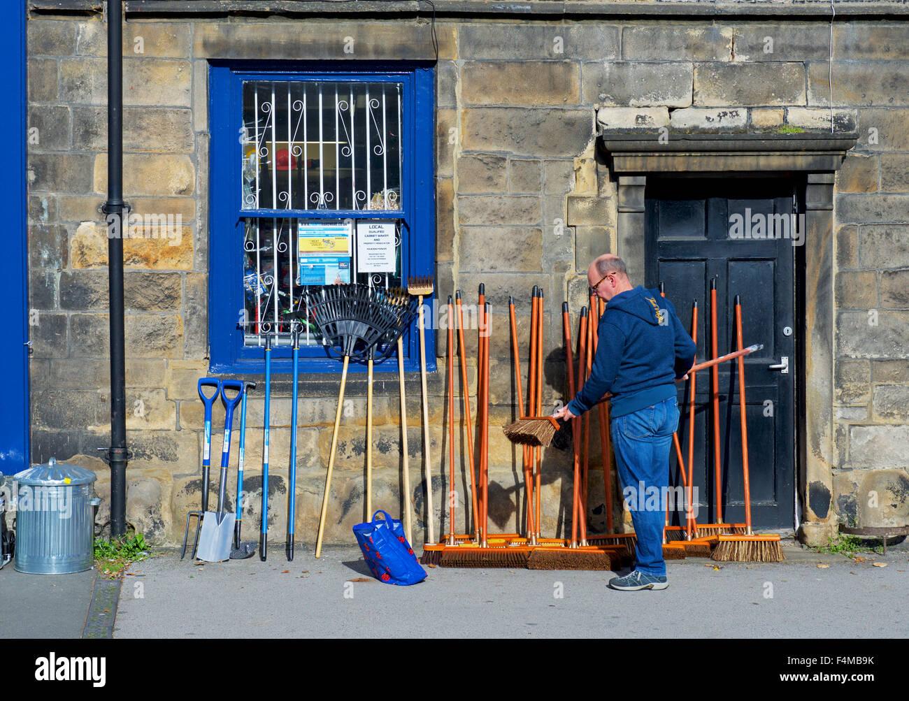 El hombre eligiendo una escoba fuera de una tienda en Otley, West Yorkshire, Inglaterra Imagen De Stock