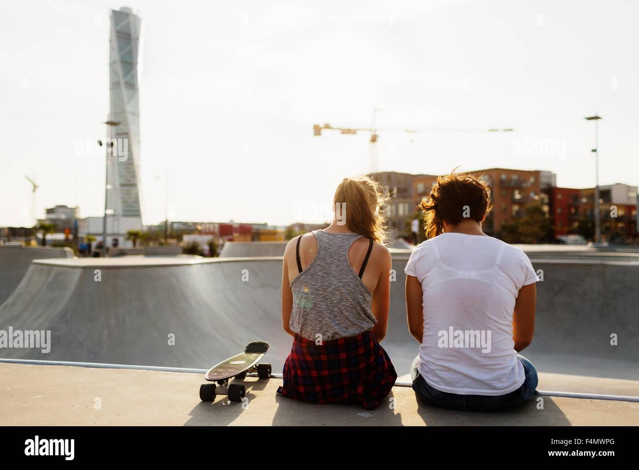 Vista trasera de amigas sentada en el borde de la rampa de skate Imagen De  Stock a03b536f6f3