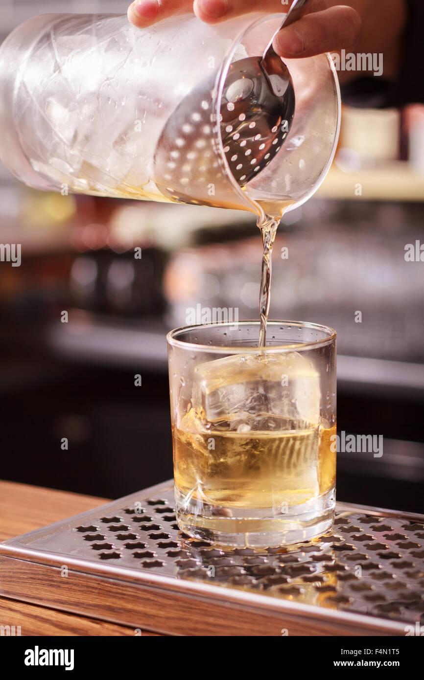 Barman haciendo cóctel en una barra. Imagen De Stock