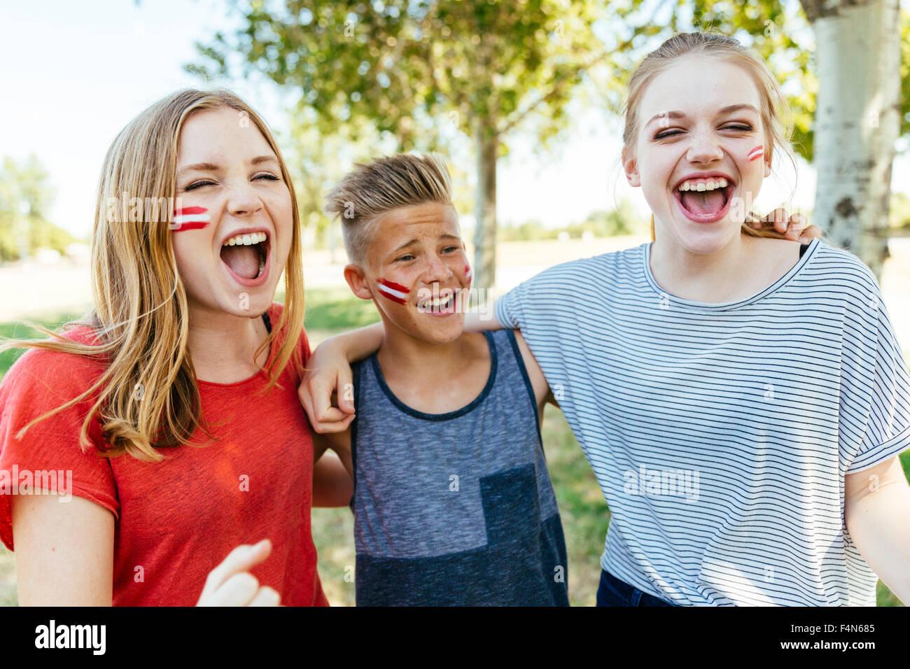 Austria, tres adolescentes con colores nacionales pintados en sus mejillas celebrando juntos Imagen De Stock
