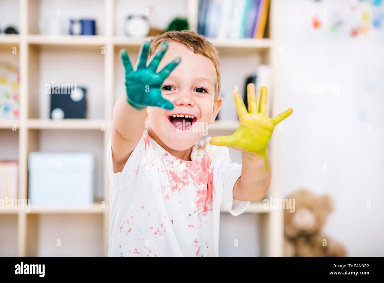 Retrato de niño sonriente mostrando sus manos pintadas Imagen De Stock