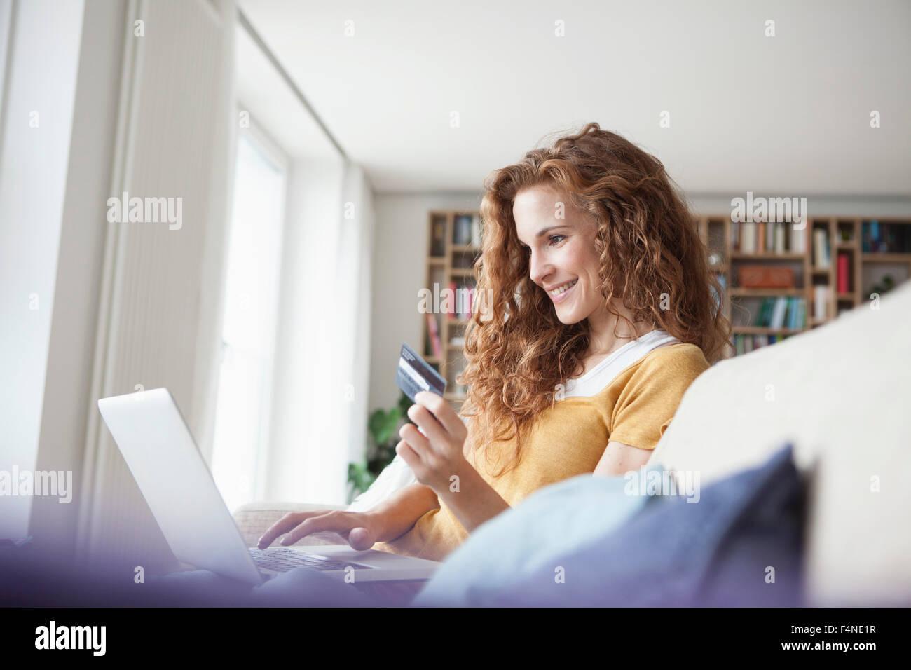 Mujer sonriente en casa compras online Imagen De Stock