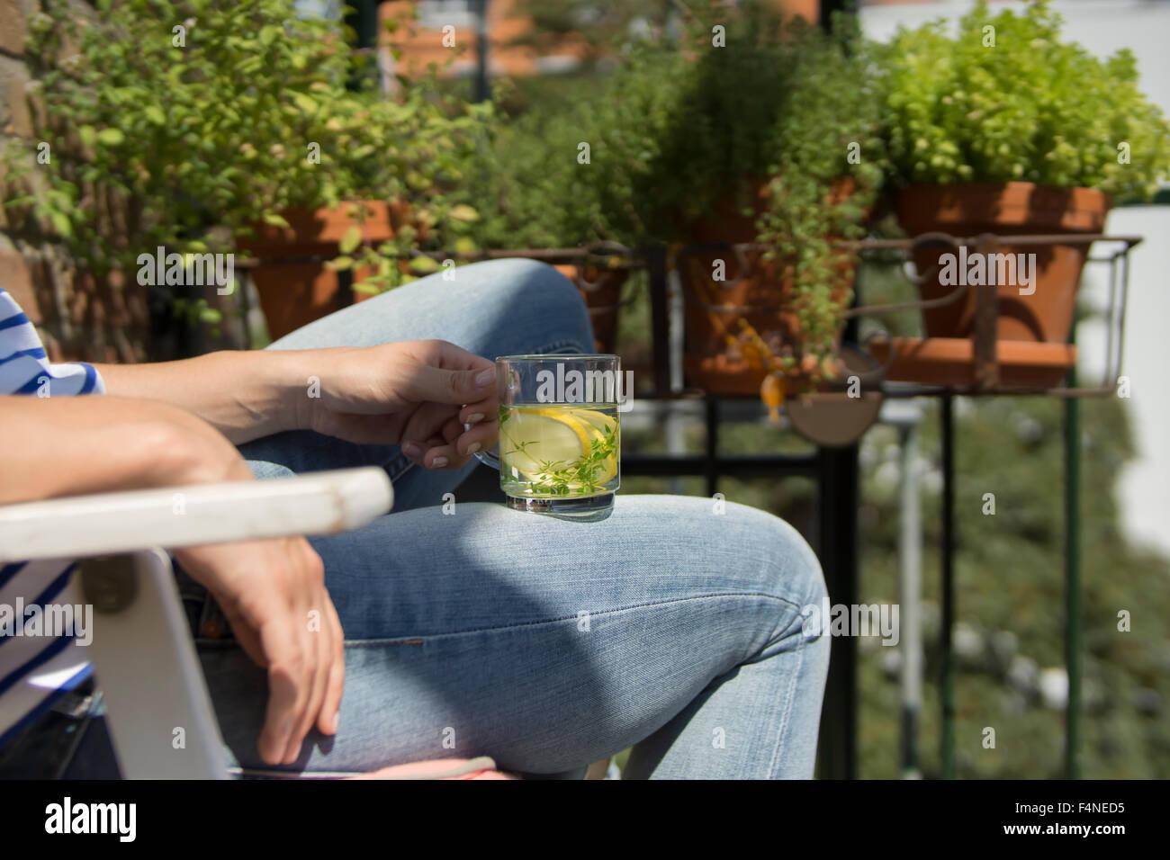 Mujer joven sentada en el balcón, bebiendo té Imagen De Stock