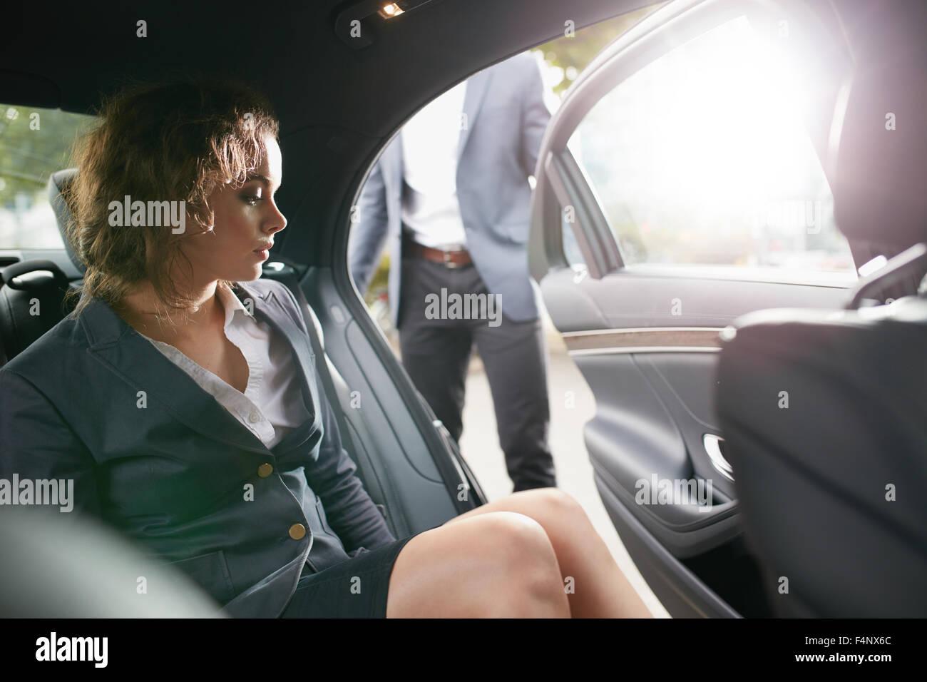El hombre la apertura de una puerta del pasajero para una empresaria salir de un coche. Emprendedor femenino viaja Imagen De Stock