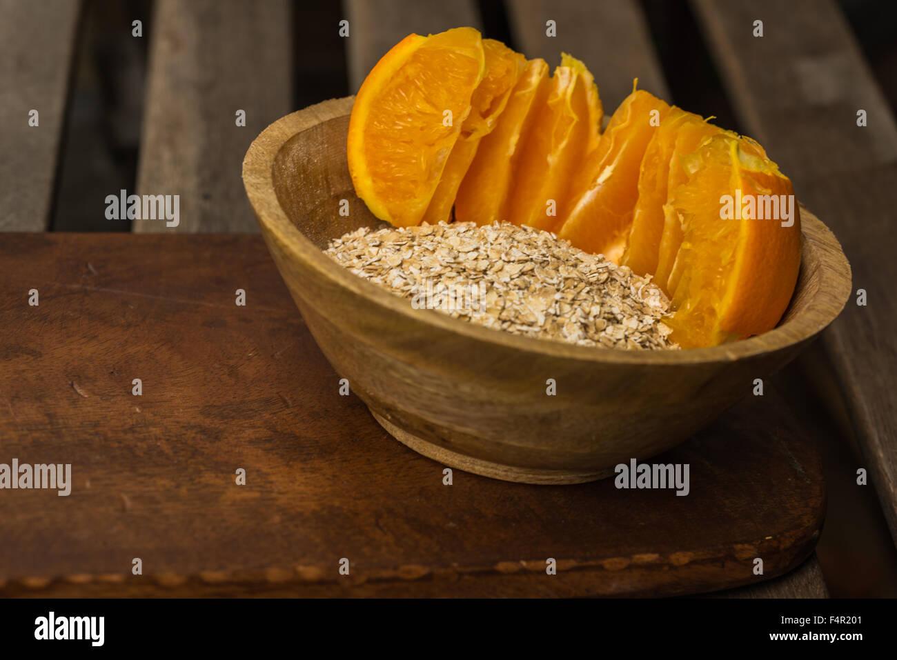 Los copos de avena y naranja en un tazón de desayuno saludable - Sinergia de alimentos, añada agua o  Imagen De Stock