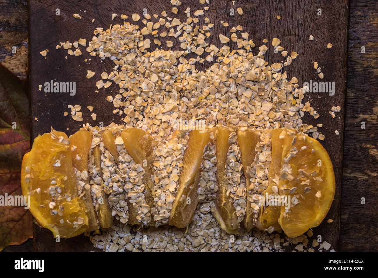 Los copos de avena y naranja sobre una tabla de cortar de madera - Sinergia de alimentos, comida sana combinación Imagen De Stock