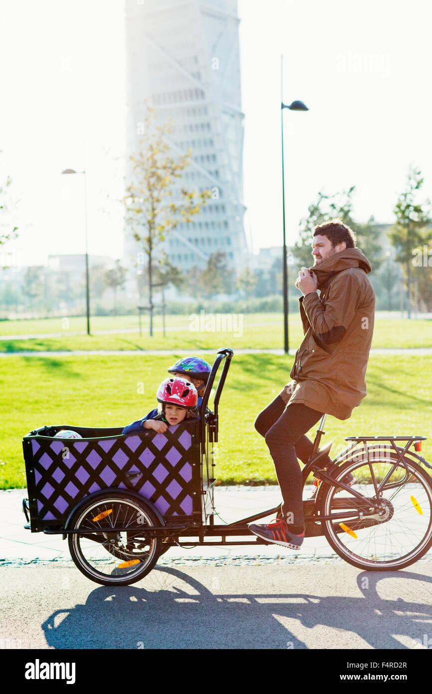 Suecia, Skane, Malmo, Vastra Hamnen, Padre hijos de conducción (4-5 y 6-7) en triciclo en el parque urbano Imagen De Stock