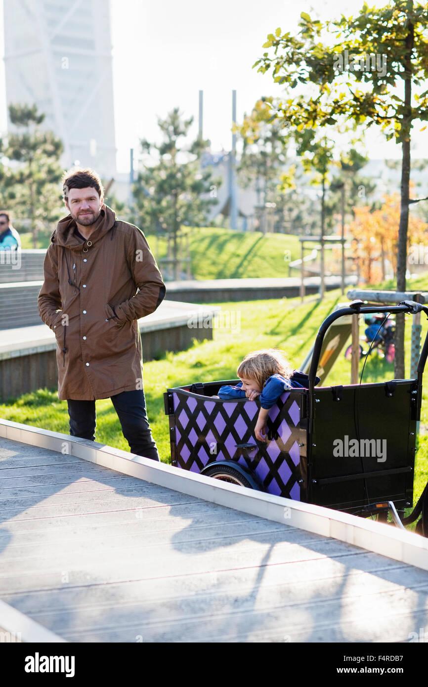 Suecia, Skane, Malmo, padre hijo de conducción (6-7) en el parque urbano Imagen De Stock
