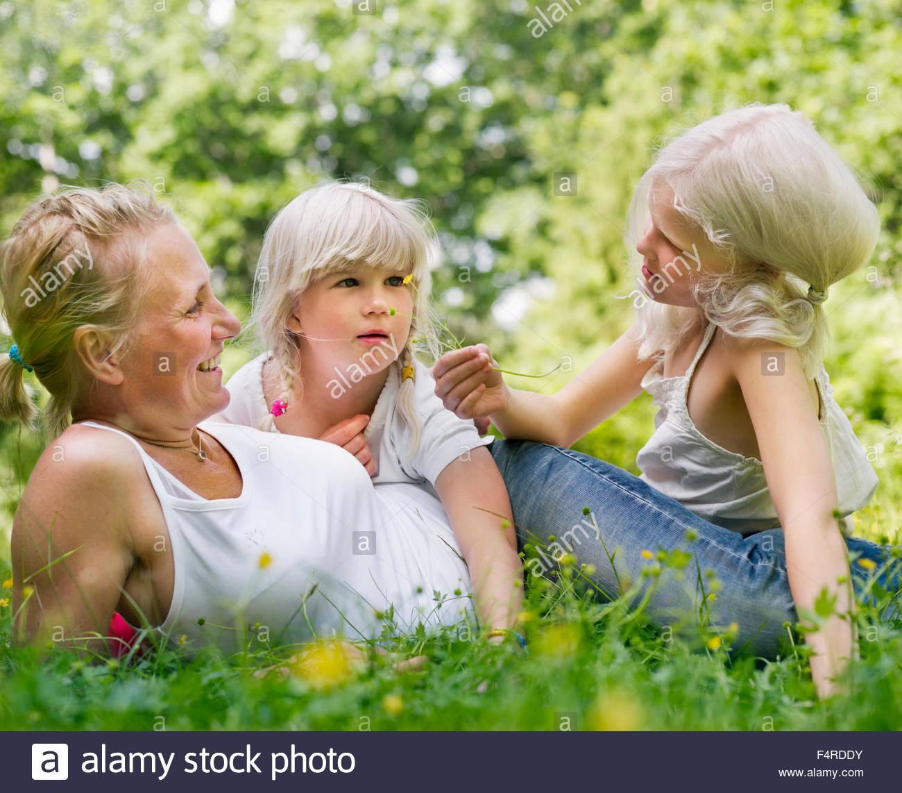 Madre de dos hijas (8-9) de relax en el parque local. Imagen De Stock