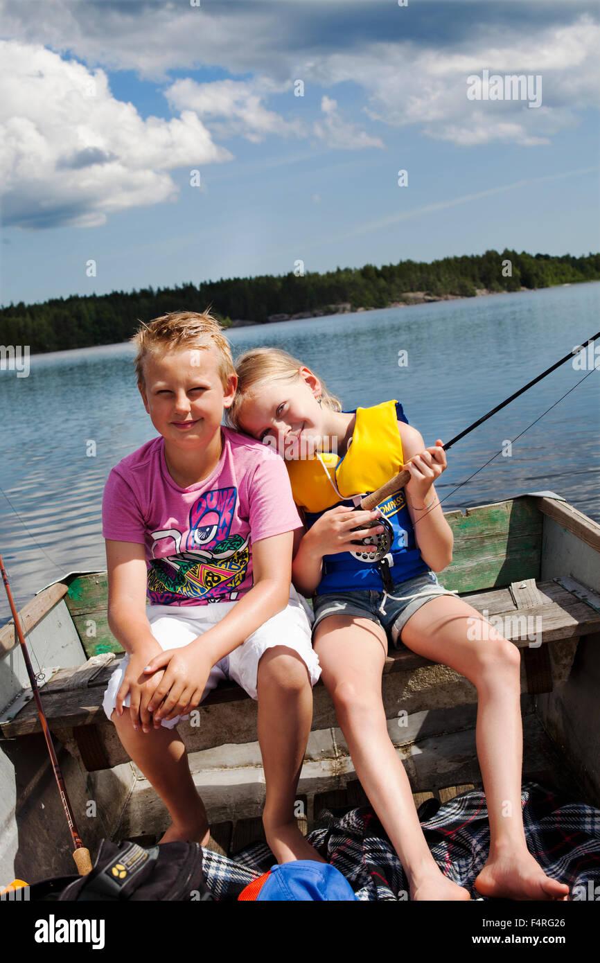 Niña y Niño (8-9, 10-11) la pesca en el lago Imagen De Stock